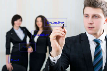 delivers: Young businessman delivers the concept to co-workers writing the chart on the screen board Stock Photo