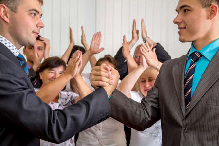 adult  male: High school graduates shaking hands while happy parents and grandparents applauds on the background