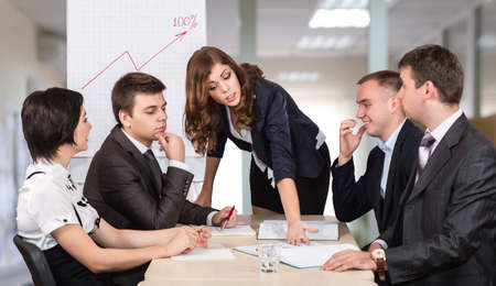 dissatisfied: Dissatisfied manager Severe female corporate manager criticizes the member of her team while others are ironically observing this scene Stock Photo