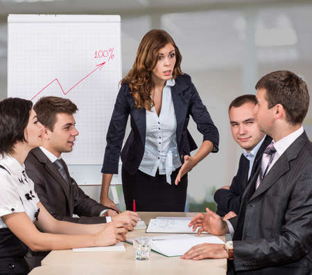 criticizes: Dissatisfied manager Severe female corporate manager criticizes the member of her team while others are ironically observing this scene Stock Photo