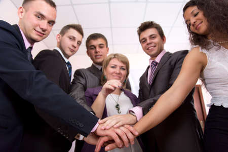 harmonious: Friendly harmonious business team Six business people join hands and smiling. Focus is on hands, but face expression is recognisable