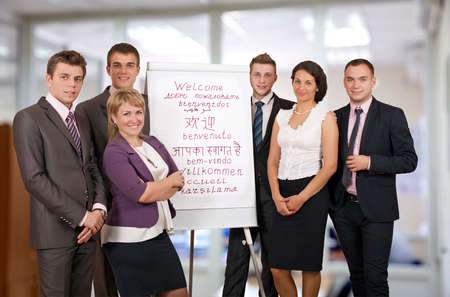 Team of six business consultants welcomes participants of conference business looking people stay next to flip chart with WELCOME sign written in many languages 스톡 콘텐츠