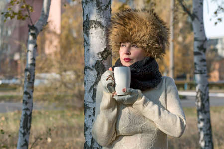 european white birch: Northern beauty Lady dressed in traditional northern hat and scarf stays between birches and drinks coffee