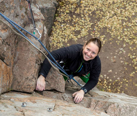 crack climbing: Smiling female climber and her ropes Blond smiling female climber climbs the wall