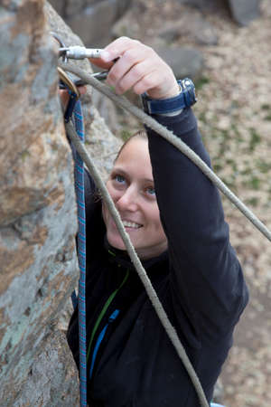 belaying: Blond female climber and her gear Smiling female climber links the rope to belaying devise