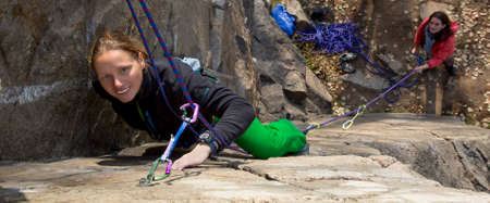 belaying: Female climbers Two female rock climbers. Blond climber is leading, brunette climber is belaying. Narrow horizontal composition fits most of website headers
