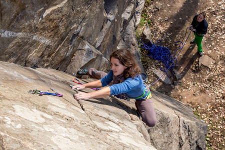 crack climbing: Pair of female climbers assault the rock wall Nice female climber makes difficult move on the climbing wall. Her partner keeps rope and belays