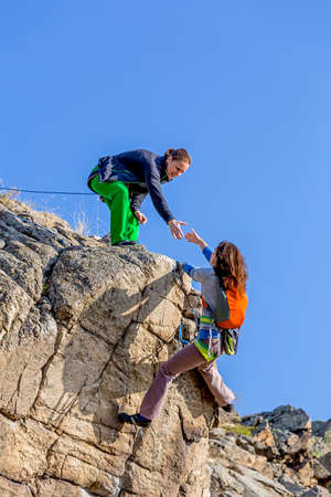 Climber aiuta il suo compagno ai ricchi i summit di due scalatori di sesso femminile, un trascina la mano di un altro. Profondo cielo blu sullo sfondo Archivio Fotografico - 43391625