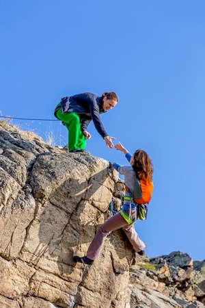 escalando: Escalador ayuda a su pareja a los ricos cumbre Dos escaladores femeninos, uno arrastra la mano de otro. Cielo azul profundo en el fondo