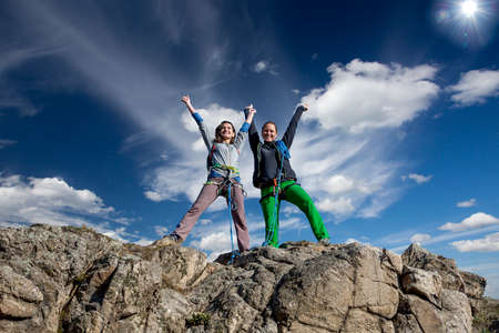 conquered: Group of two happy female climbers that are just conquered the summit Blue cloudy sky and sun on the background
