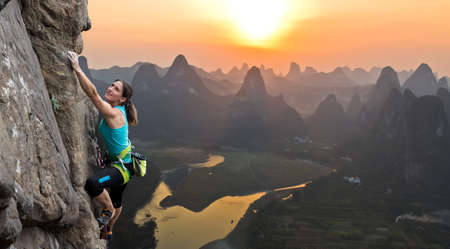 Silhouette of female athlete on Chinese mountain sunset Elegant slim body of woman hanging on her hand on rock wall unusual China landscape with river karst mountains and sunset on background