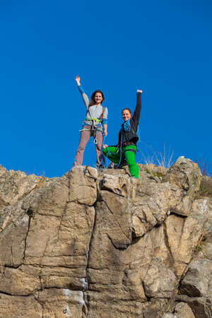 conquered: Group of two happy female climbers that are just conquered the summit stays over the rocky wall blue sky background