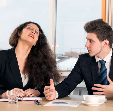 disagreed: Disagreed female executive and young employee Bored, disagreed female boss and male businessman who tries to convince her. Office interior, conference table, window on the background Stock Photo