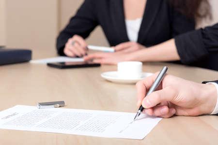 contrato de trabajo: Mujer firma contrato businessperson Primer plano de la mano femenina firma de papel formal sobre la mesa de la oficina. La contraparte de negocios en el fondo