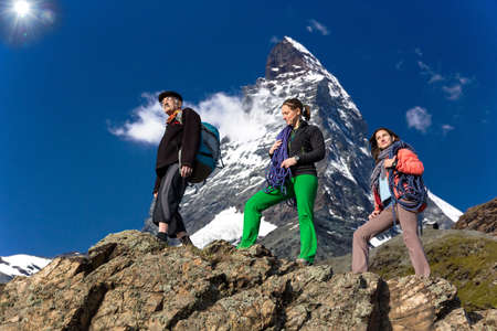 farther: Team of climbers walks against alpine background Farther and daughters walk on the mountain ridge. High alpine landscape on the background Stock Photo
