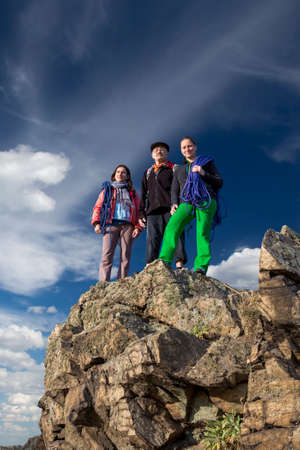 abyss: Group of climbers stays on the pointed cliff Family of father and two daughters stays on the rocky cliff that sharply breaks to the abyss