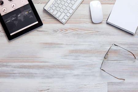 木製テーブルのタブレット、キーボード、マウス コンピューター、メモ帳が付いているオフィスできれいな、よく組織化の作業スペースに上からビ