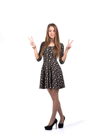 Young lady showing VICTORY sign with her hands Young caucasian female makes positive gesture with her both hands, full body portrait on white background with some shadow on the floor