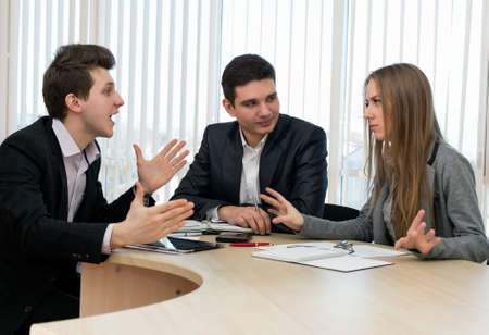 Group of three people having discussion Office Interior Charts and Paperwork on Desk Business people tries to convince each other making eloquent gestures