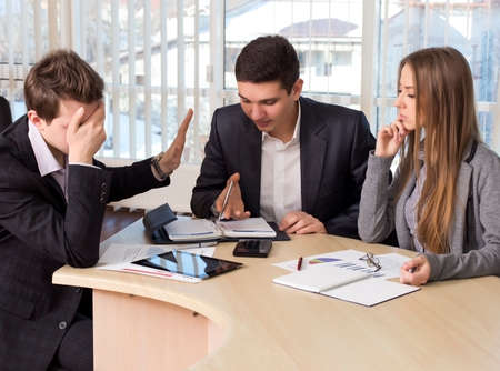 Bored manager Group of business people on the meeting. Male participant rejects the offer and makes closing his face with the hand Stock Photo