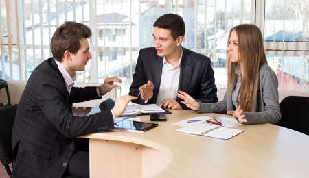convince: Group of three people having discussion Office Interior Charts and Paperwork on Desk Business people tries to convince each other making eloquent gestures