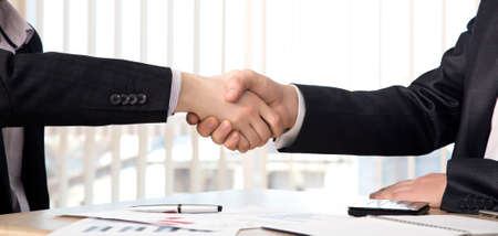Handshake of business partners Hands of casually dressed males. Business background with some charts and office supplies on the table Stockfoto