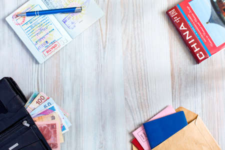 china stamps: The composition of essential items for trip: passport with multiple entry stamps, cash notes from different countries, wallet and envelope, folded map of China, on wooden background Stock Photo