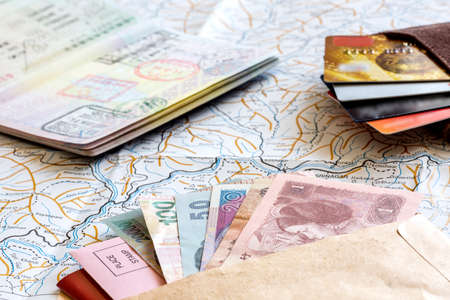 The composition of essential items for trip: passport with multiple entry stamps, cash notes from different countries, wallet and envelope, folded map of China, on wooden background Standard-Bild