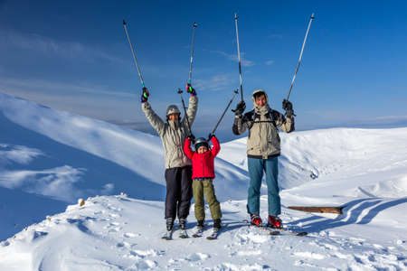 Winter sport family Family of three people - parents and little daughter - on winter mountains background