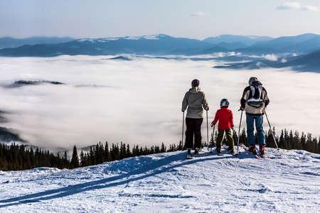 山の風景 3 人の家族を観察することの人々 は、風光明媚な風景の手前に表示します。これらはスキーヤー、彼らは冬のスポーツ ジャケットに身を包
