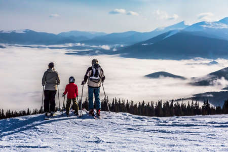 snow ski: People observing mountain scenery Family of three people stays in front of scenic landscape. These are skiers, they dressed in winter sport jackets and have skies attached