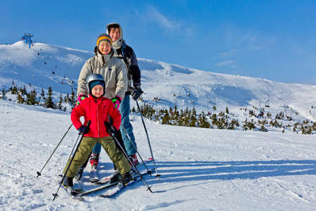Family of three people learns skiing together Mixed race family stays on the snow slope with the skis attached. Happy, smiling, joyful