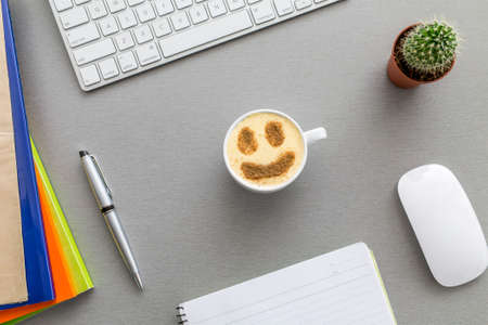 Office work space grey desk with cactus and cappuccino from above view grey wooden desk well organised office supplies mug with cappuccino chocolate smiley surface
