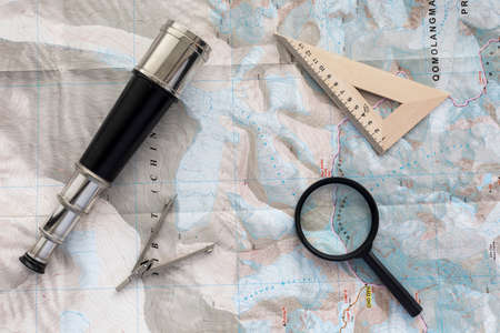 Desk of explorer Top view of desk covered with the topographic map with typical items navigator: sea telescope, navigational triangle, magnifier and compass Stock Photo