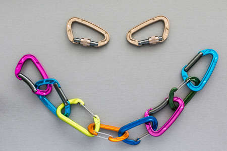 Smiley shape completed with alpine climbing carabiners Many coloured extreme climbing carabiners linked in the chain and forming the smiley shape. Two separate carabiners form an eyes of face Stock Photo