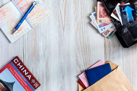 Desk of frequent traveler The composition of essential items for trip: passport with multiple entry stamps, cash notes from different countries, wallet and envelope, folded map of China, on wooden background Standard-Bild