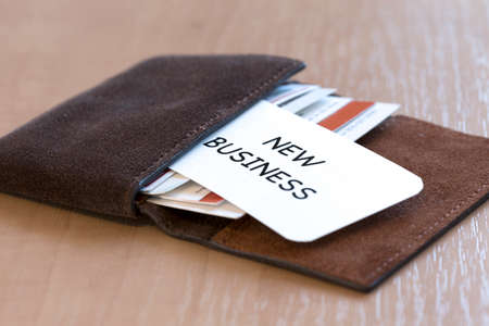 businesscard: New business Conceptual composition with leather business-card folder, stack of colourful business cards and white business card with phrase New Business on foreground Stock Photo