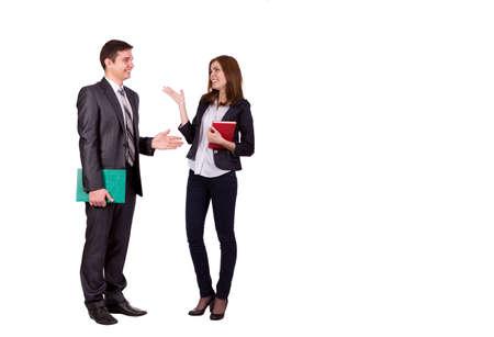 Conversación emocional masculino joven y femenina, vestidos oficialmente, discutiendo y haciendo gestos mano. Retrato de cuerpo entero en el fondo blanco Foto de archivo