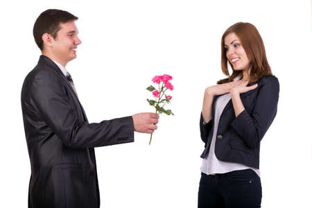 dress code: Pleasant gift Young man gives a branch of flowers to beautiful lady. She expresses pleasure and delight. White background. Official dress code