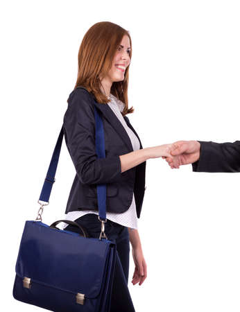 charismatic: Portrait of charismatic female business person Image of beautiful and energetic caucasian female, smart casual style dressed, shaking hand of counterpart and carrying her blue business style bag on her shoulder Stock Photo