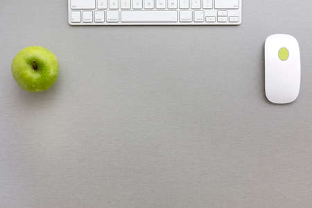 Espacio de trabajo en la composición de estilo oficina creativa de color gris-verde con verde manzana y teclado de la computadora y el ratón se encuentra en el escritorio de madera gris. Vista superior