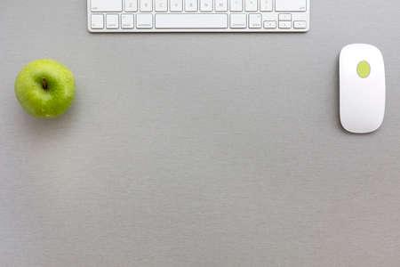 teclado: Espacio de trabajo en la composición de estilo oficina creativa de color gris-verde con verde manzana y teclado de la computadora y el ratón se encuentra en el escritorio de madera gris. Vista superior