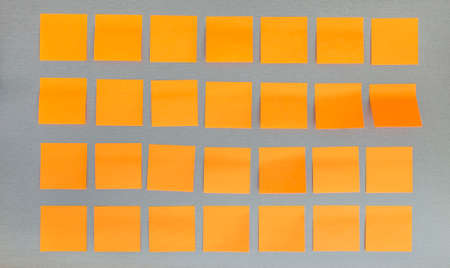 attached: Dark grey notice board with many blank orange paper stickers attached to it