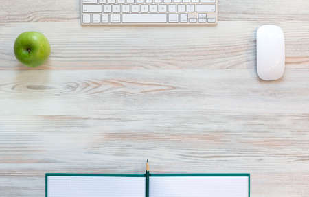 klawiatura: Biurko z zielonym jabłkiem Widok z góry na jasnym beżowym drewniane biurko z zielonym jabłkiem, duży notatnik, komputer klawiatury i myszy, zielonym ołówkiem