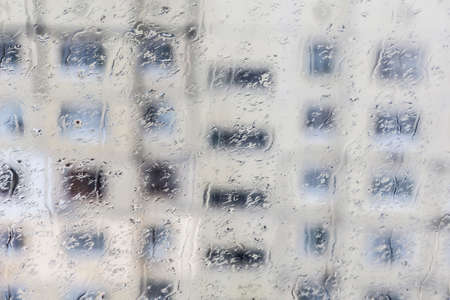 trickles: Raindrops on the window Drops and trickles of rain on the window. Blurred urban background