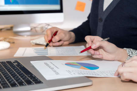 emphasise: Hands of people working on presentation Office desk with laptop and large screen on the foreground, male and female hands keeping pens and pointing on the data charts Stock Photo
