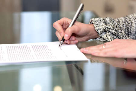 Lady signs contract Close up of female hand signing formal paper on the glass table Stock Photo