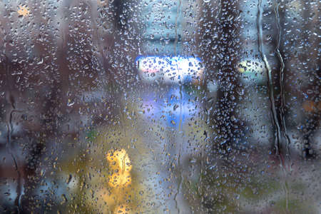 trickles: Raindrops on the window with evening city lights Drops and trickles of rain on the window. Soft colored evening city lights on the background
