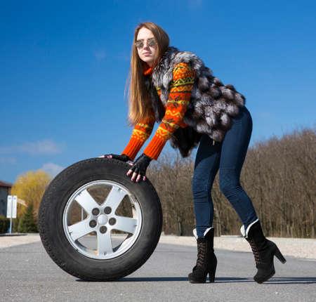leggy: Leggy beautiful female holds big wheel Portrait of stylish, elegant lady rolling big tired wheel across the highway. Outdoor scene, blue sky, sun shining day