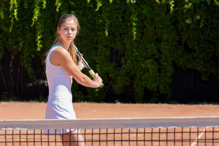 tennis skirt: Young tennis athlete ready to return a ball Elegant girl tennis white dress with skirt swinging racket to hit coming ball green fence background